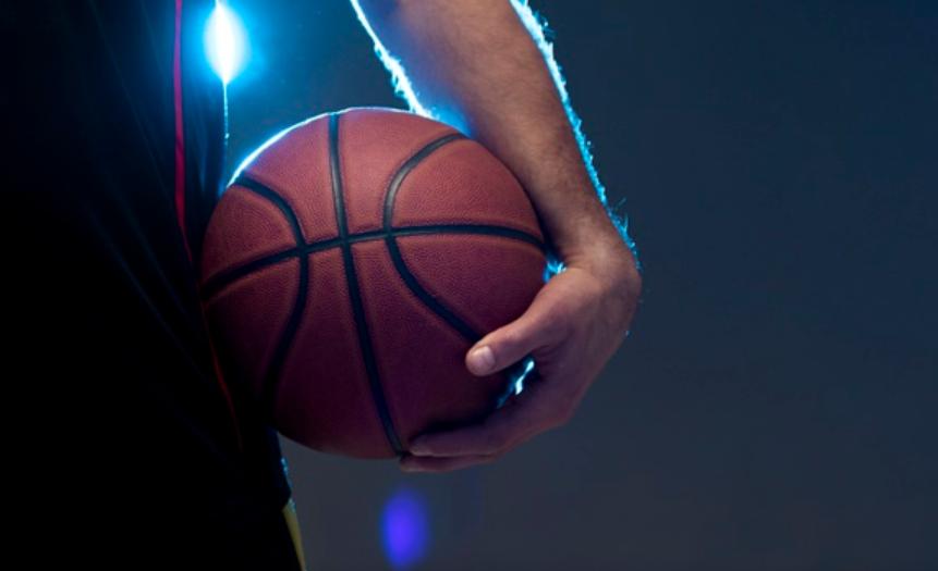 homem branco segurando uma bola de basquete na altura da cintura com a mão esquerda