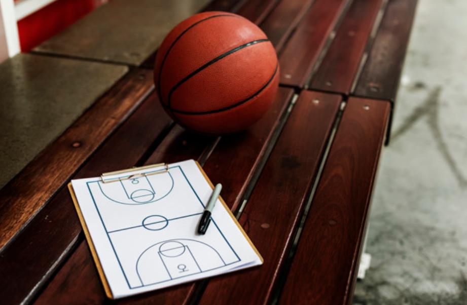 bola de basuqte e tabela com desenho de uma quadra em um banco de madeira