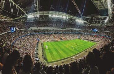 imagem panrâmica de estádio de futebol com o campo em foco e a torcida ao redor