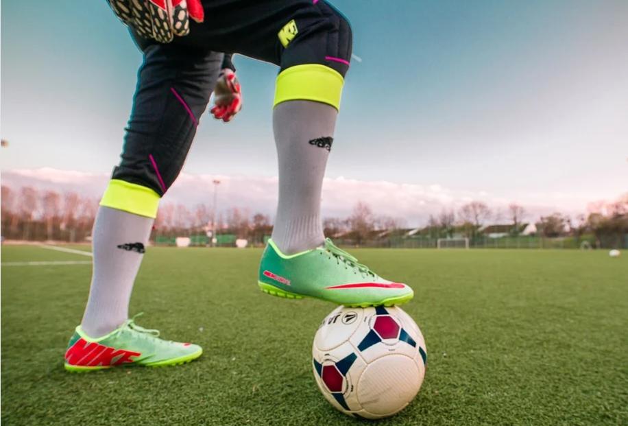 homem de calça preta usando luvas de goleiro e chuteira verda apoiando a perna sobre uma bola de futebol