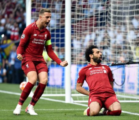 Mohamed Salah usando uniforme vermelho e comemorando realização de gol durante a última das finais da champions league