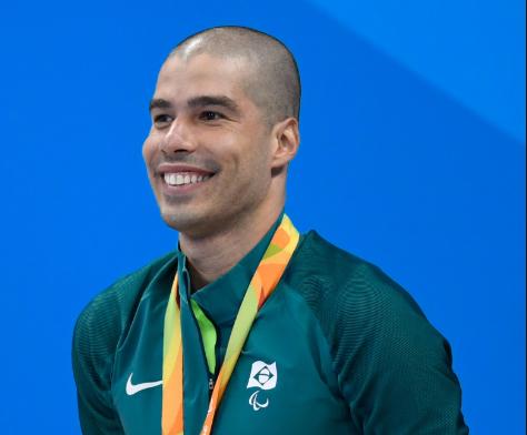 Daniel Dias sorrindo em cima do pódio de uma competição vestindo um casaco verde