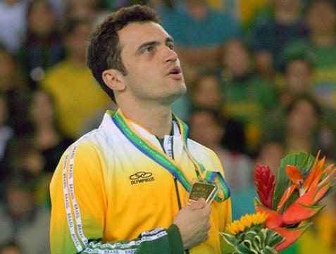 """Falcão """"12"""" cantando o hino nacional em cima de um pódio segurando um bouquet de flores e uma medalha"""