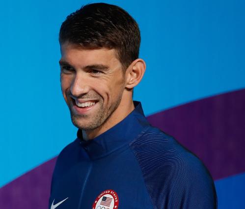imagem do atleta michael phelps sorrindo usando um casaco azul