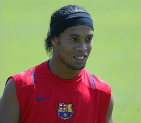 Ronaldinho Gaúcho usando uma regata de treino vermelha com o símbolo do Barcelona