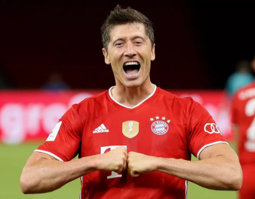 Robert Lewandovsky usando uniforme do Bayern de Munique sorrindo e encostando as mãos serradas uma na outra
