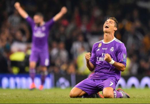 Criatiano Ronaldo, de uniforme rocxo, comemorando a vitória em final da champions league