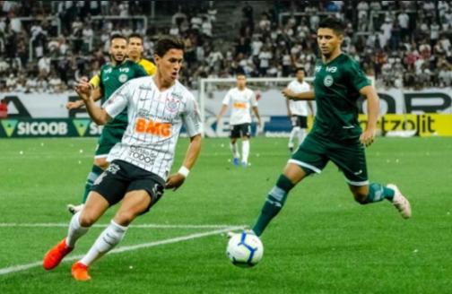 atleta uando uniforme preto e branco correndo com a bola contra dois atletas usando uniformes verdes em um campo de futebol