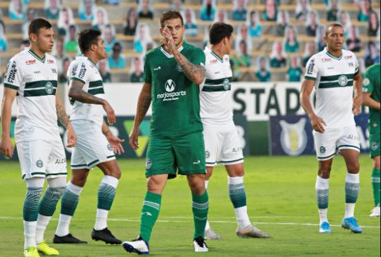 atleta usando uniforme verde levando a mão à cabeça na frente de quatro atletas uniformizados de branco