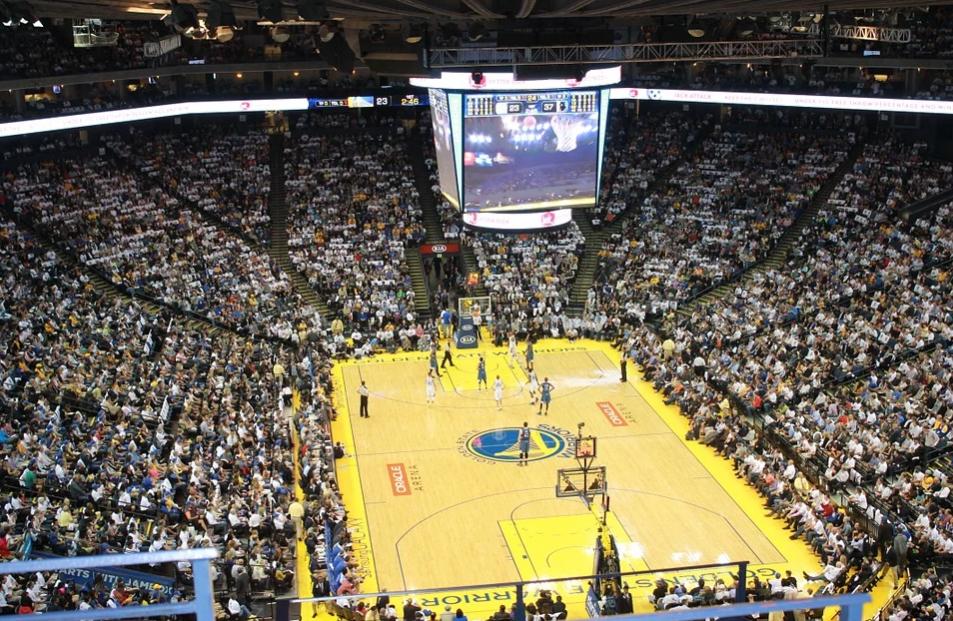 imagem de quadra de basquete amarela com jogadores vista de cima com plateia nos arredores
