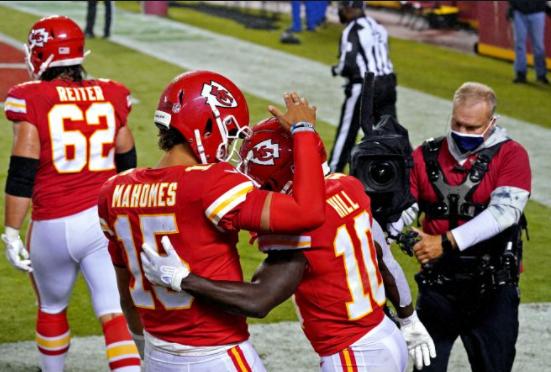 atletas de futebol americano usando uniformes vermelhos e se abraçando em frente a um homem que os filma dentro do campo