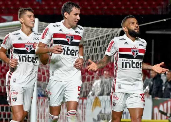 jogadores do São Paulo caminhando em trio pelo campo após realização de gol