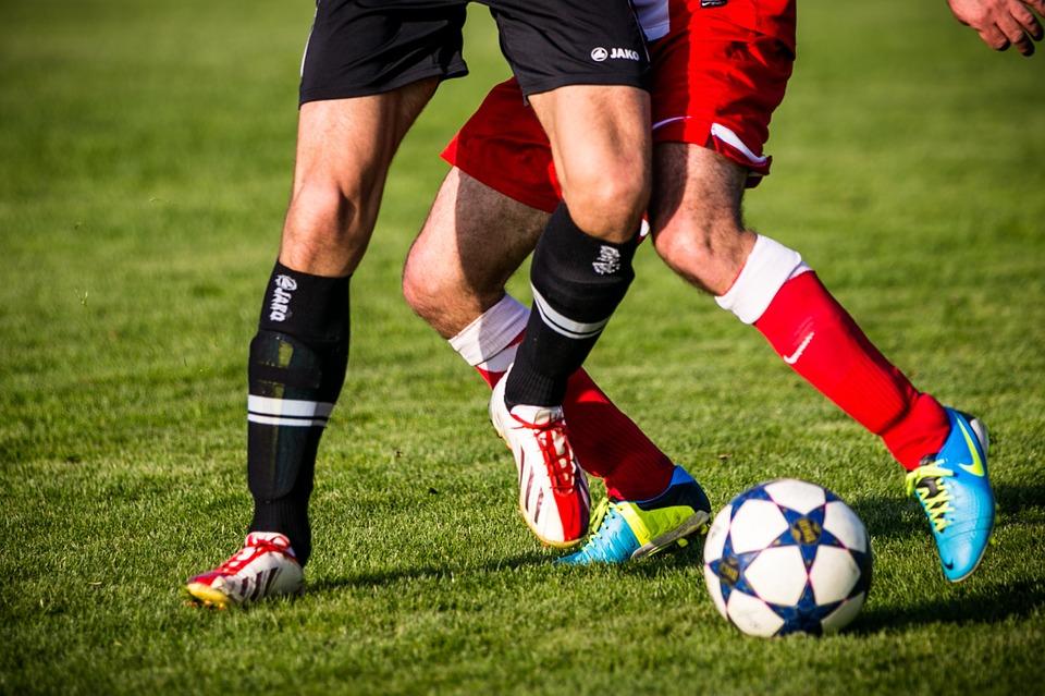 atleta de vermelho marcando atleta de uniforme preto