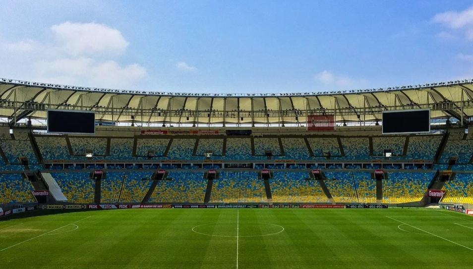 estádio de futebol com gramado verde e arquibancadas nas cores azul e amarelo