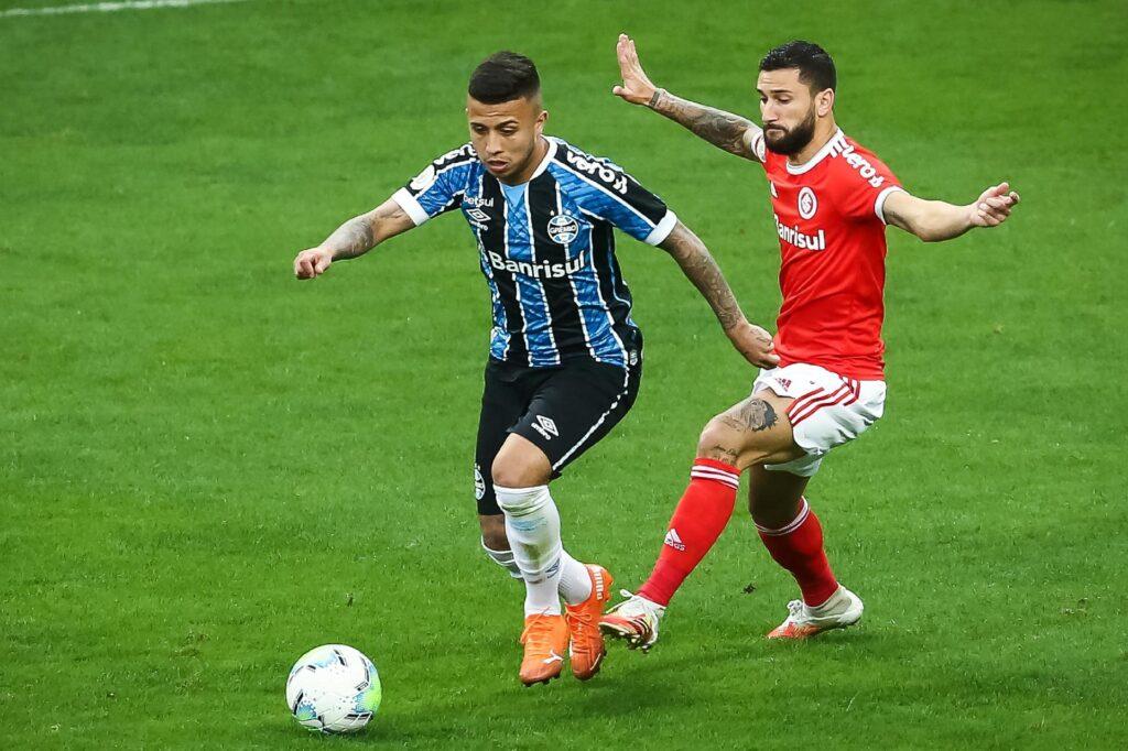 imagem de atleta do grêmio usando uniforme azul e preto correndo com bola nos pés sendo marcado por atleta do internacional usando uniforme vermelho