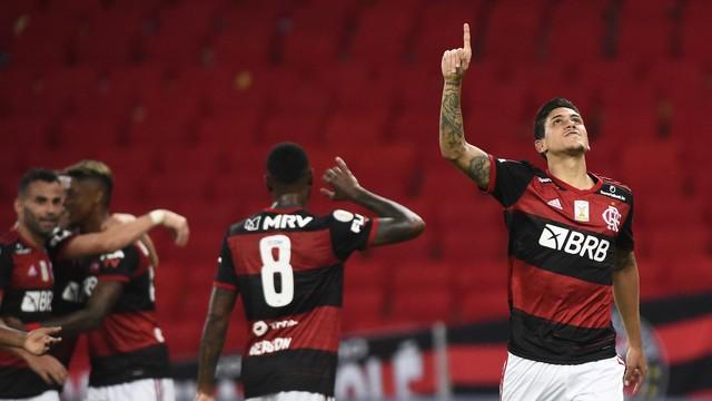 atleta do flamengo usando uniforme preto e vermelho ergue a mão para o alto a frente de outros jogadores durante jogo