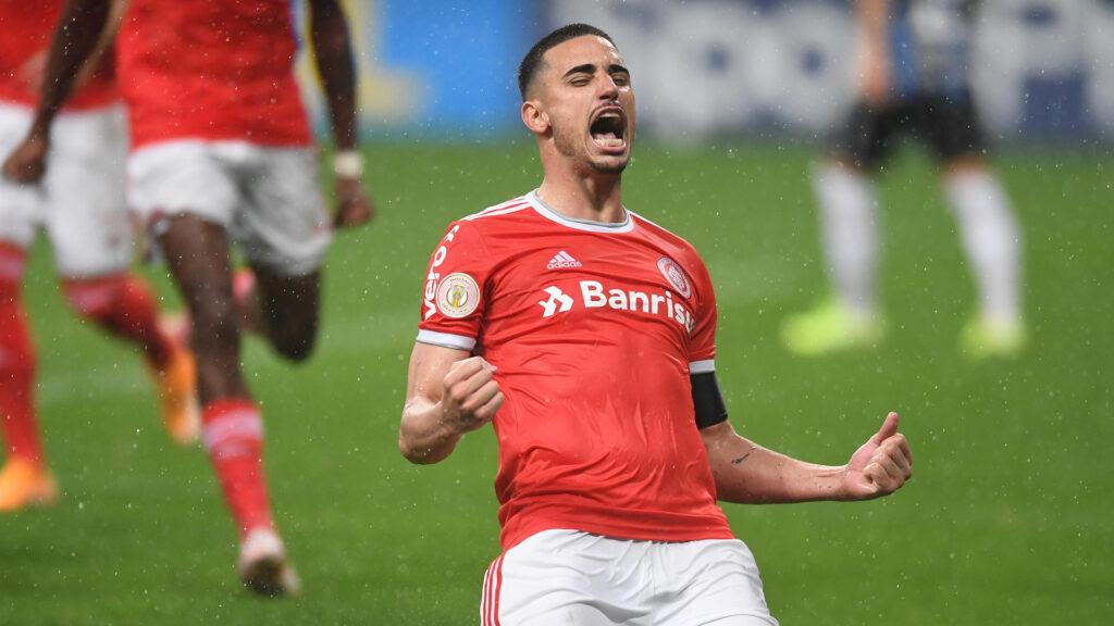 atleta do internacional usando uniforme vermelho e branco comemorando gol durante jogo