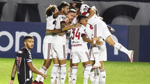 atletas do flamengo usando uniforme branco se abraçam em grupo após vitória em jogo