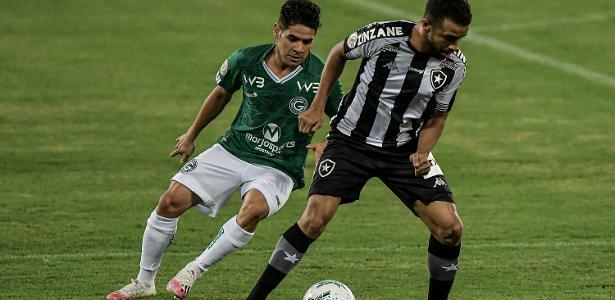atleta do botafogo usando uniforme preto e branco sofre marcação de atleta do Goiás com uniforme verde