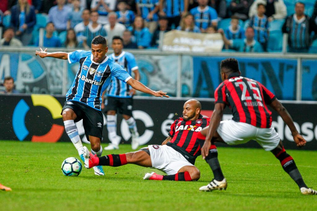 atleta do Atlético Goianiense aplica carrino para recuperar bola enquanto jogador do Grêmio tenta driblar com a perna direita