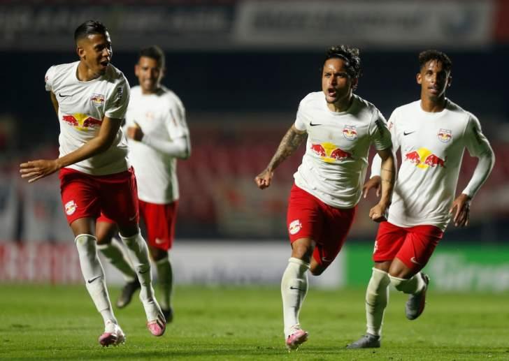 Atletas do bragantino usando uniforme vermelho e branco celebram gol durante partida
