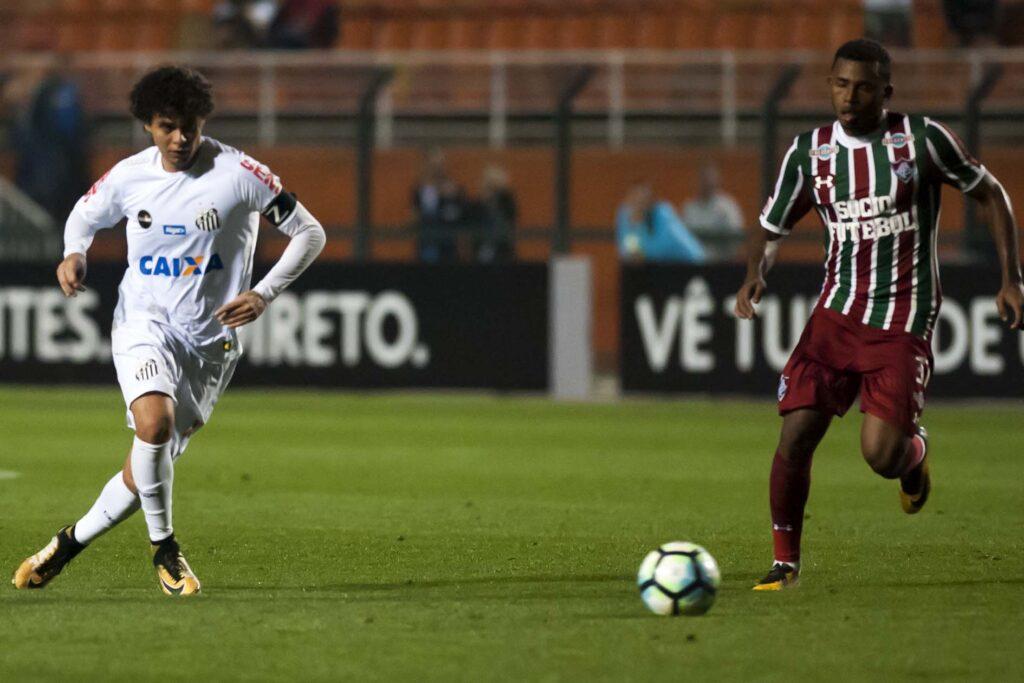 Atleta do Santos e do Fluminense correm em direção a bola durante partida