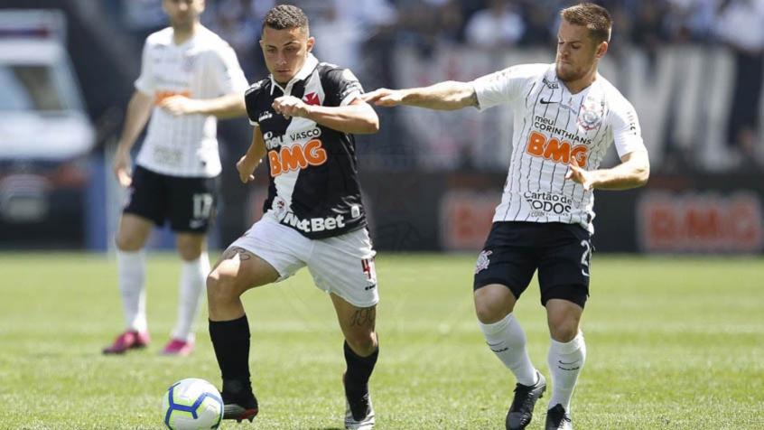 jogadores do Vasco e do Corinthians usando uniformes preto e branco disputando bola em campo