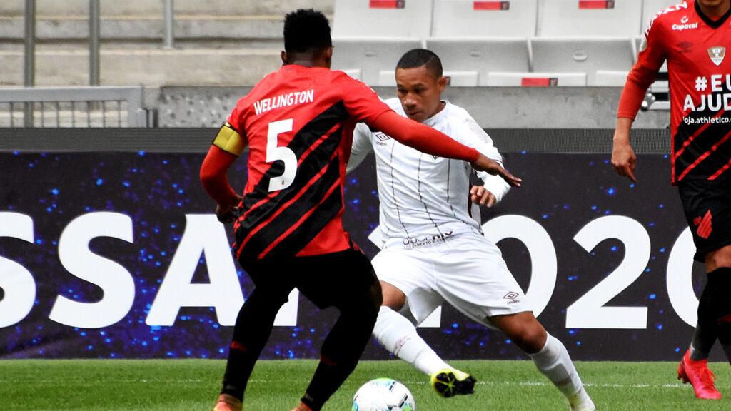 Atleta do Fluminensa usando uniforme branco dribla jogador do Atlético Paranaense que usa uniforme preto e vermelho