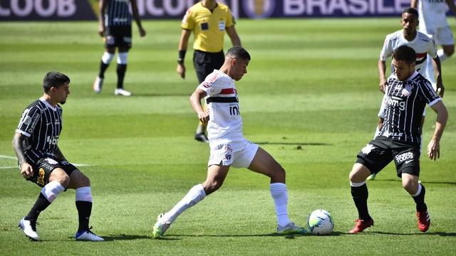 atleta do São Paulo usando uniforme branco é marcado por dois atletas do Corinthians usando uniforme preto