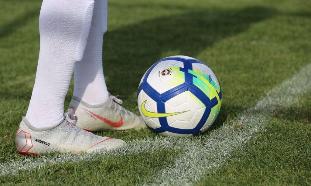 imagem aproximada de bola de futebol dentro de campo ao lado de pés com chuteira branca de atleta de futebol