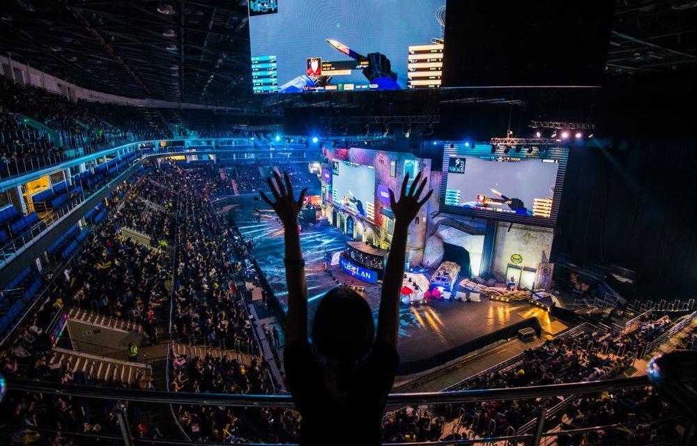 em primeiro plano um jovem ergue as mãos para cima durante partida de e-sports