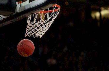 imagem de bola de basquete passando pelo aro e rede de uma cesta em jogo