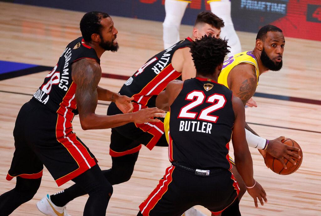 em jogo das finais da NBA atleta dos lakers usando uniforme amarelo e roxo é marcado por atletas do miami heat que usam uniforme preto e vermelho