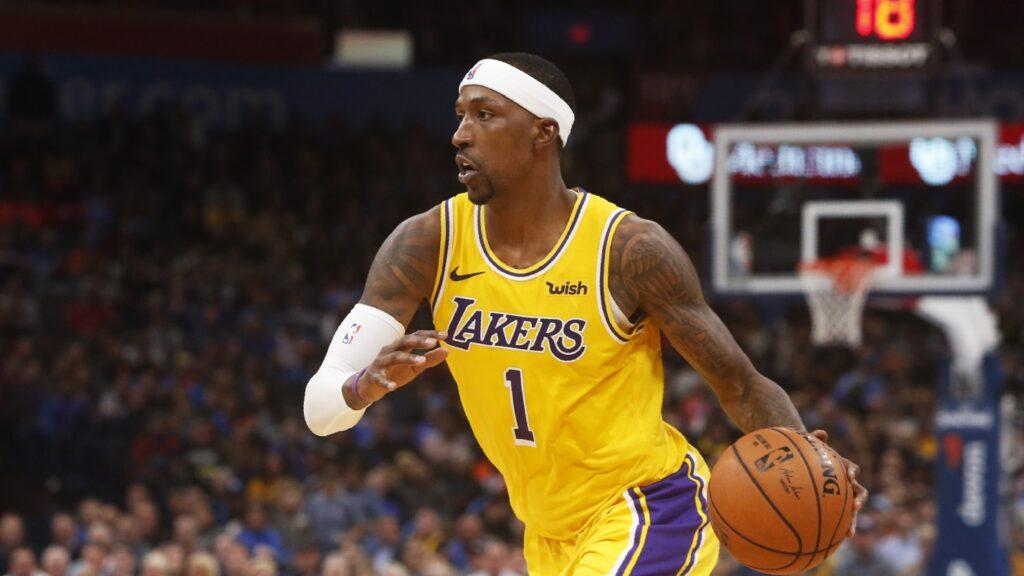 Kentavious Caldwell-Pope usando uniforme amarelo dos Los Angeles Lakers e uma faixa branca na cabeça corre com a bola durante partida