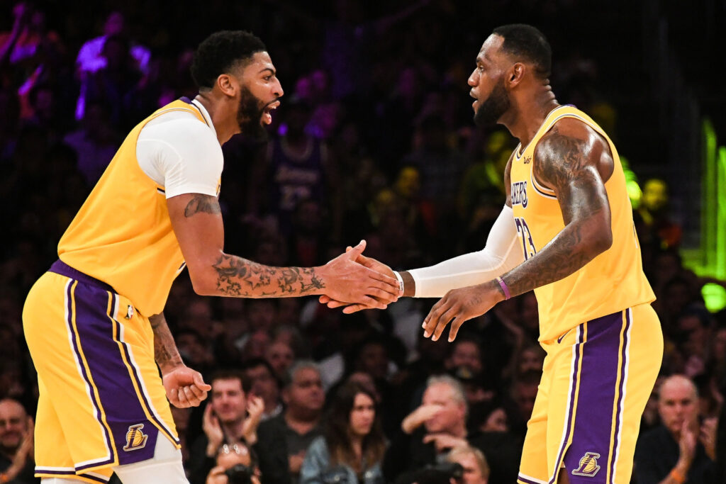 Lebron James e Anthony Davis vestindo uniforme amarelo do Los Angeles Lakers se cumprimentam após ponto durante partida