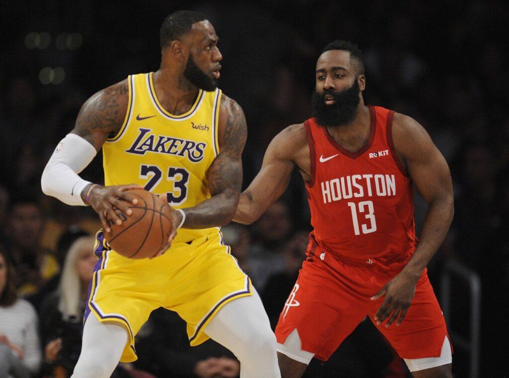 Jogador dos Loas Angeles Lakers usando uniforme amarelo sofre marcação de atleta do Houston Rockets de uniforme vermelho durante partida