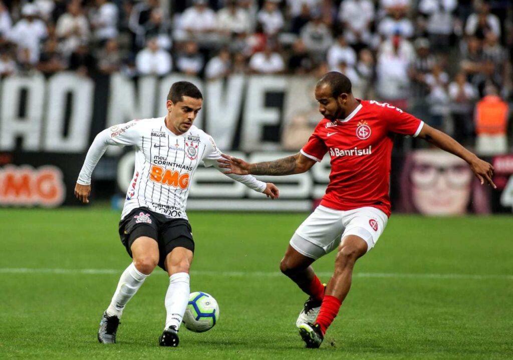 Atleta do corinthians usando uniforme branco com shorts preto dominando bola e sendo marcado por atleta do internacional que usa uniforme vermelho com shorts branco