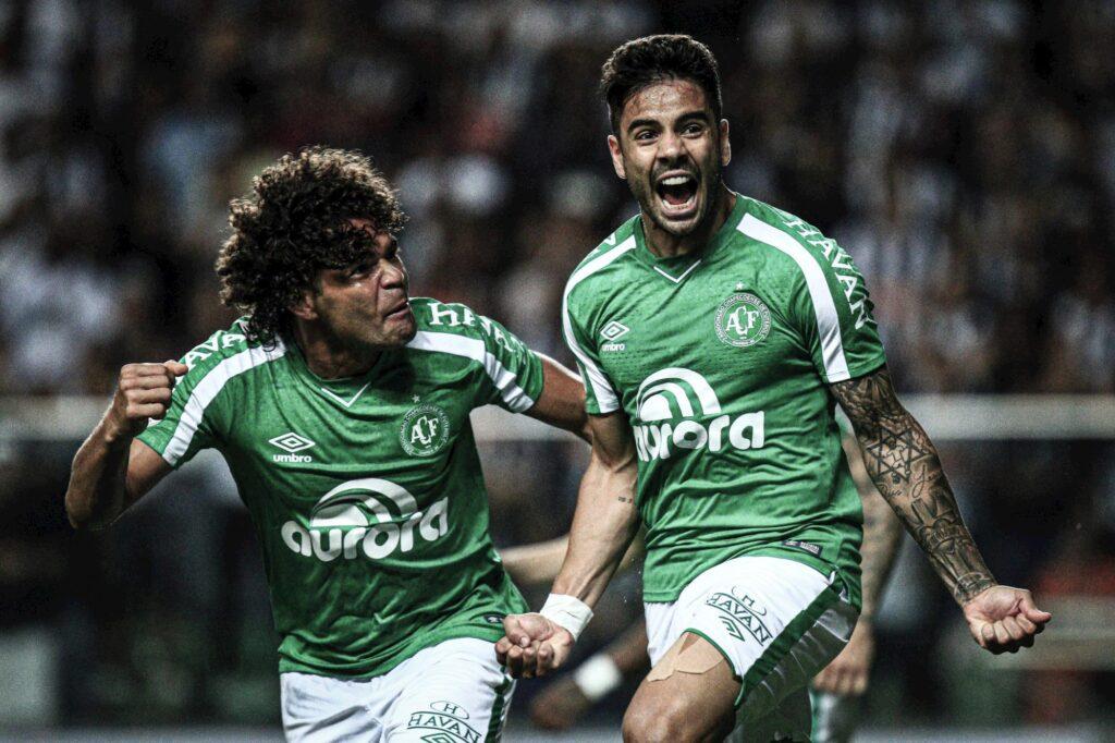 imagem de atletas da chapecoense usando uniforme verde correndo em campo comemorando gol durante partida