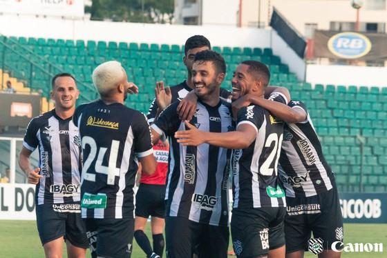 Atletas do Figueirense usando uniforme preto e branco se abraçam durante partida comemorando gol