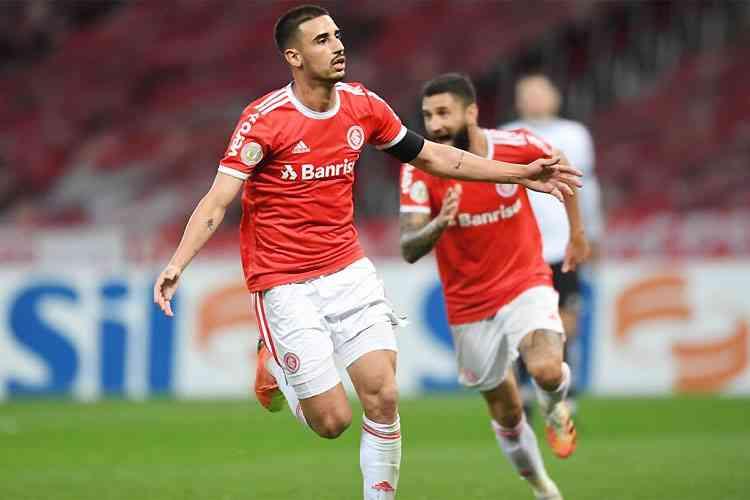 thiago galhardo usando uniforme vermelho e branco do internacional corre pelo campo comemorando gol sendo seguido por companheiro de time que corre e comemora junto