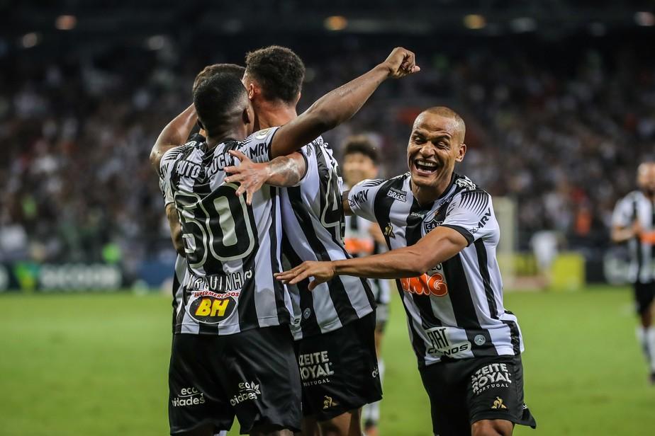 durante jogo, três atletas do atlético mineiro usando uniforme preto e branco se abraçam comemorando gol