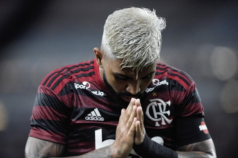 imagem do atleta Gabigol usando uniforme preto e vermelho do flamengo junta as mãos e as leva ao rosto