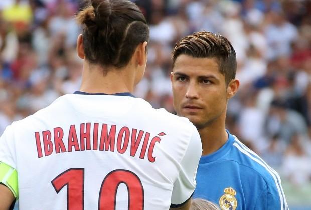 Ibrahimovic de costas usando uniforme branco com escrita vermelha em frente a Cristiano Ronaldo que usa uniforme azul com símbolo do Real Madrid