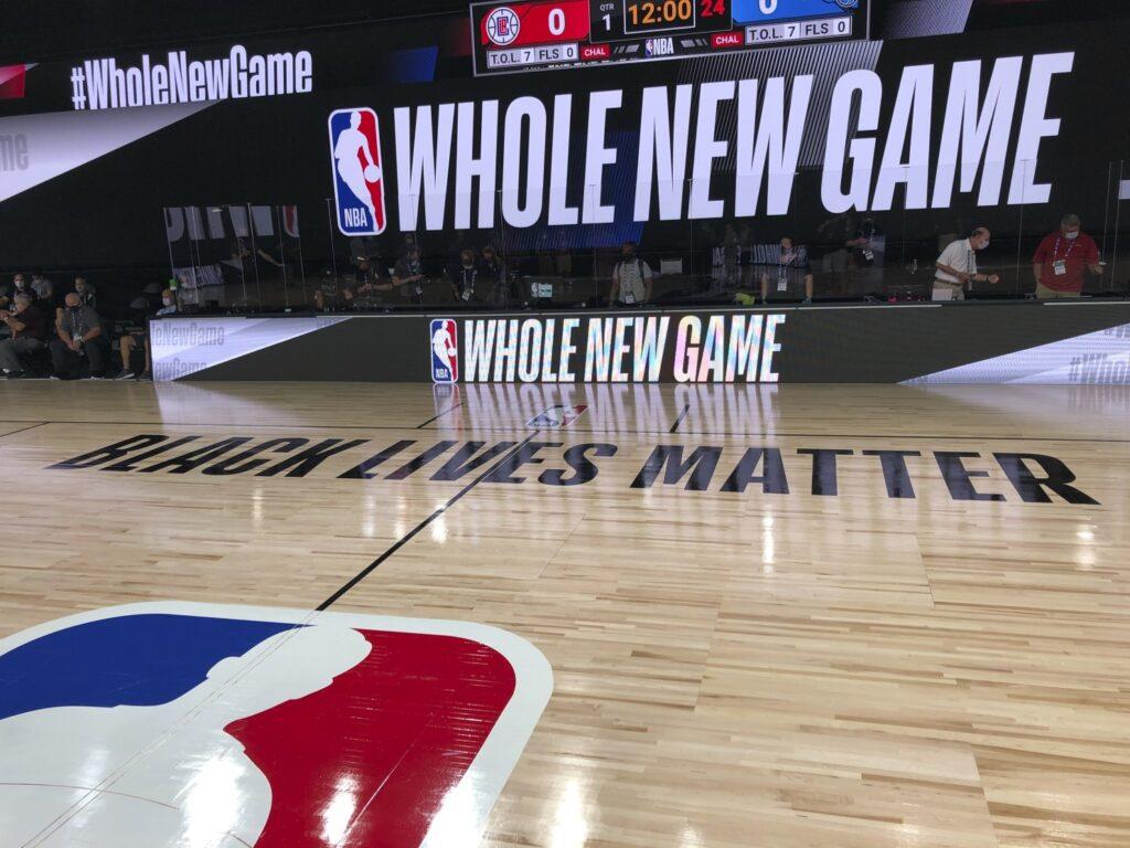 """imagem de quadra de basquete dentro da bolha da disney com letreiro escrito """"whole new game"""""""