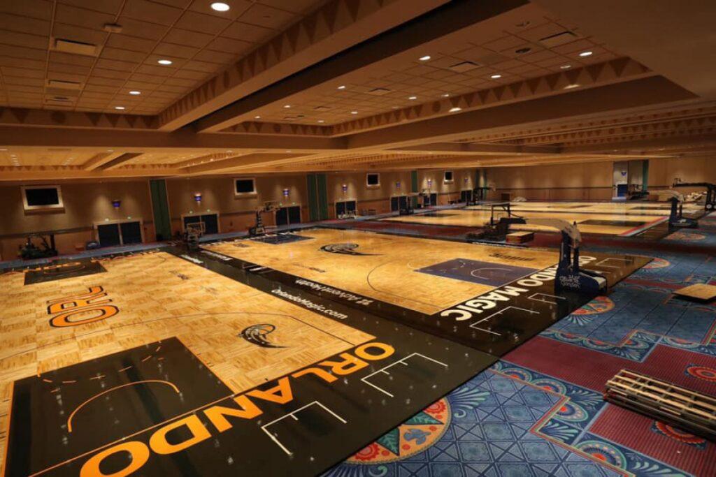 imagem da parte interna da bolha da NBA com quatro pequenas quadras enfileiradas dentro de um salão