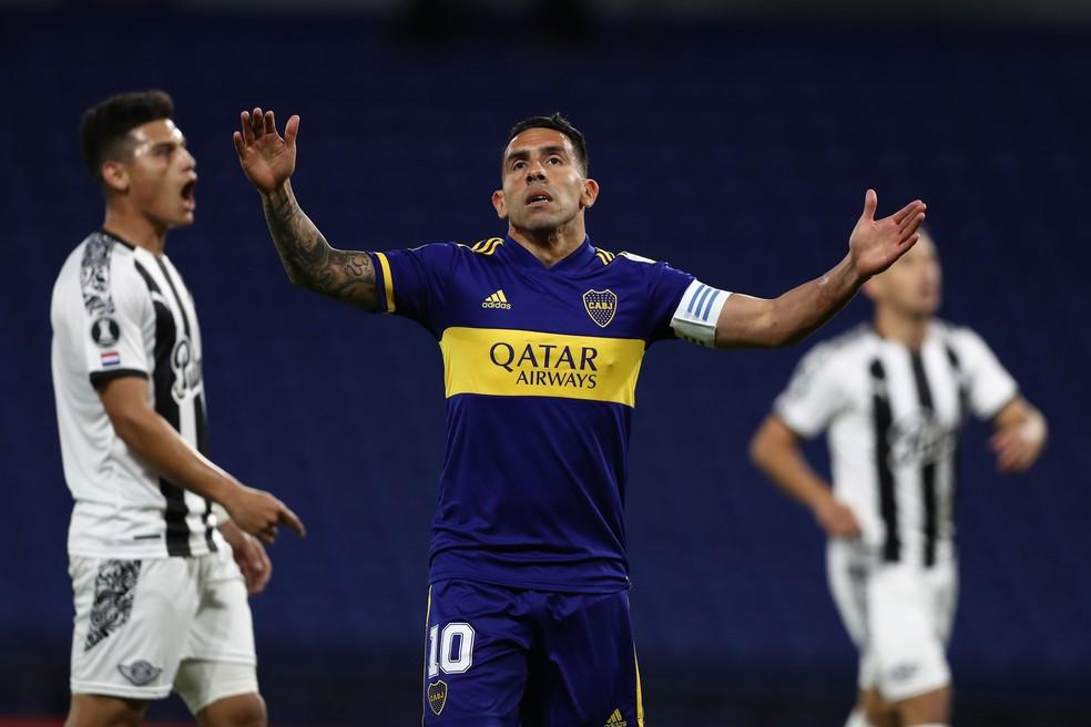 Carlitos Tévez usando uniforme azul e amarelo do boca juniors levanta braços durante jogo