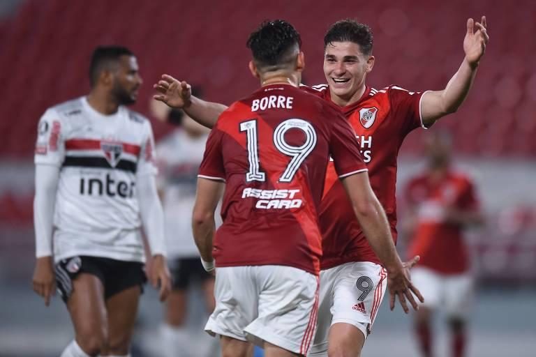 atletas do riverplate usando uniforme vermelho com shorts branco se abraçam após gol durante partida