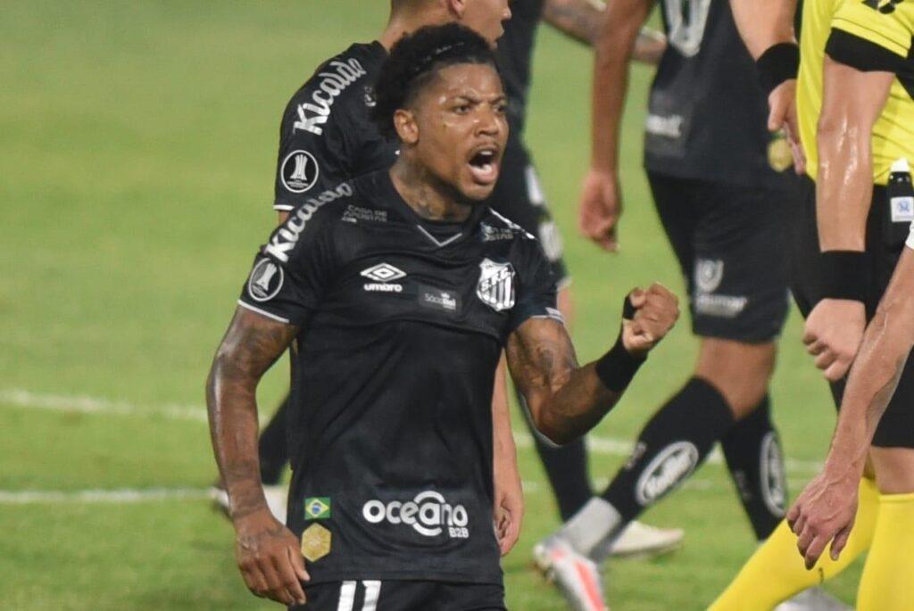Jogador Marinho do Santos usando uniforme preto comemora vitória em partida
