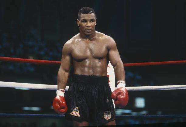 imagem de mike tyson dentro de um ringue usando luvas de boxe vermelhas antes de uma luta