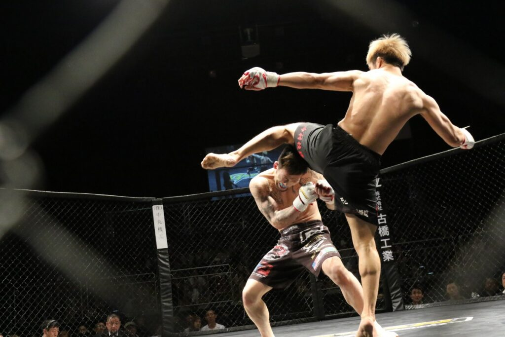 em luta de mma lutador tenta desviar de chute desferido por oponente